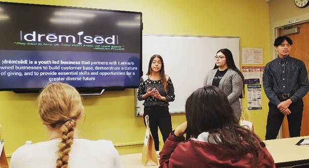 Youth from Al Éxito giving a presentation