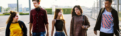 Five young people walking together