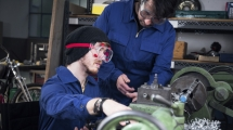 Mechanic and apprentice in wheelchair working on turning lathe