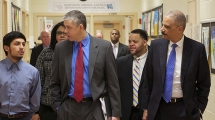 Secretary of Education Arne Duncan and Attorney General Eric Holder talking to a young student