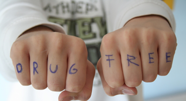 Youth with the words DRUG FREE written on knuckles